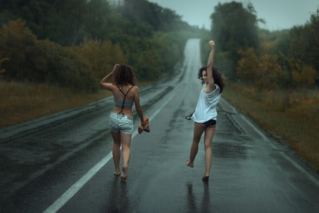sopping: Two girls are on the roadway in the rain.