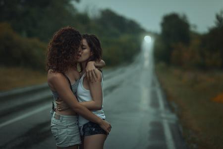 Girls lesbians kissing under the heavy rain. They got wet. Stock Photo