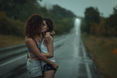 downpour: Girls lesbians kissing under the heavy rain. They got wet. Stock Photo