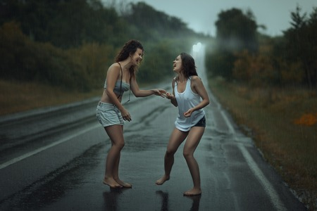 young girl barefoot: Girls standing in the rain on the roadway.