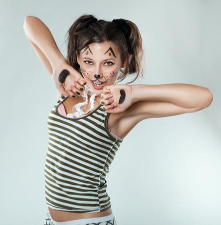 Ondeugende meisje schilderde als een kat. Geschilderde snor op zijn gezicht.