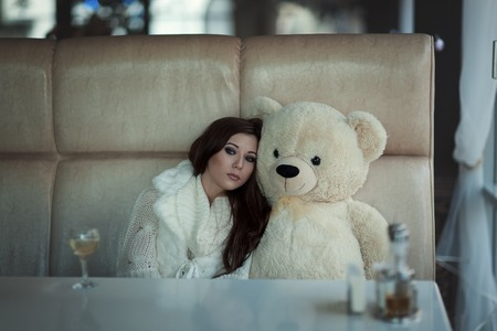 rueful: The sad girl sits at a table with a toy bear. Stock Photo