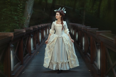 period costume: The girl in an old ball dress walking on bridge. Beautiful vintage hairstyle.