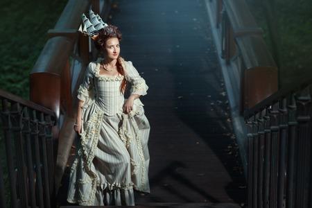 vestidos de epoca: Niña en un vestido de fiesta en las gradas. La decoración mar nave cabello.