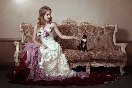 minx: Girl in a beautiful dress with a train. She is sitting on an old couch. Stock Photo