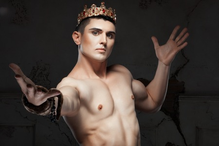 Young man with a crown on his head. His athletic body.