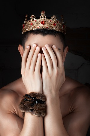 desperation: Guy with the crown on his head covered his face with his hands. Stock Photo