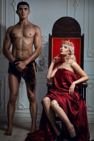 Queen sitting on a throne. Nearby is an athletic slave