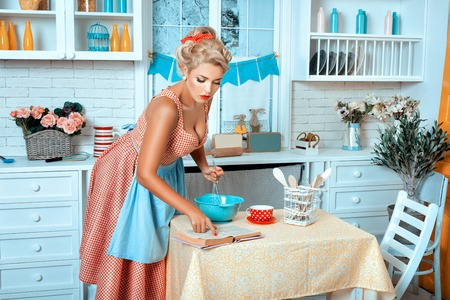 retro housewife: Girl in the kitchen reading a recipe in a book.