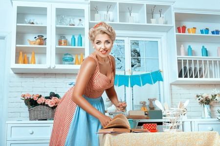 footsie: Girl in old-fashioned style, and stands in the kitchen preparing a meal.