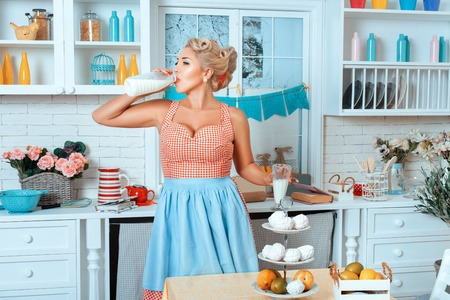 pinup girl: Girl is drinking from a glass of milk. She is in the kitchen.