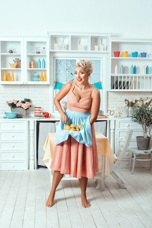 footsie: Old-fashioned woman in the kitchen holding a fruit. She is wearing an apron. Stock Photo