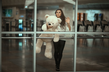 Behind the glass is a girl with a sad face. In the hands holding a toy bear.