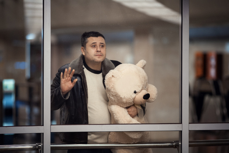 sadly: Man is holding a toy bear and looking sadly into the distance. He says goodbye.