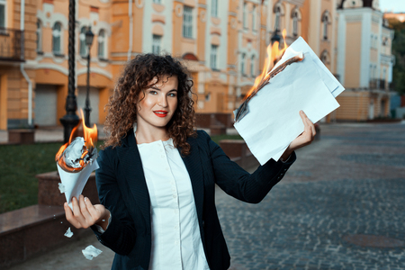 combust: Girl is holding the documents that burn. She is in the city.