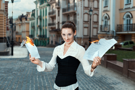 combust: Girl with joy on her face burn documents. On the streets of the city.