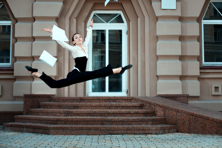 readily: Girl running down the street tossing documents handed. She is jumps high. Stock Photo