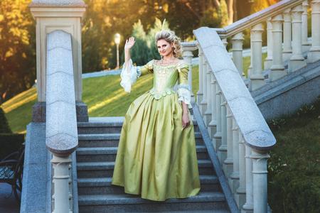 medieval dress: Chica en el vestido real de pie en la escalinata del palacio. Ella es agita su mano en se�al de saludo.