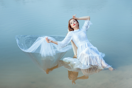 pacification: Girl sits on the lake and is reflected on the surface of the water. In her hand she had a veil.