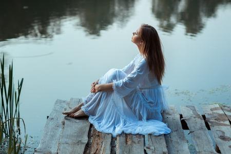 Mädchen sitzt auf einem hölzernen Pier und Träume. Am Morgen bei Sonnenaufgang Standard-Bild - 45172465