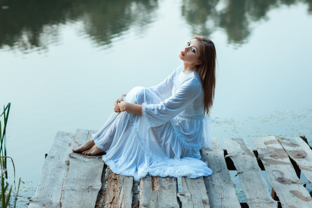 pacification: Sitting on the wharf of a beautiful girl. She is wearing a white dress. Stock Photo
