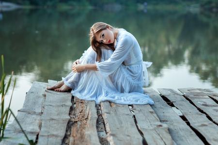 Beautiful girl sitting on the wharf bored. She wearing a white dress.