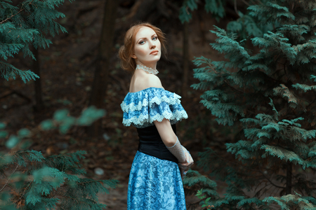 Girl dressed in an old-fashioned blue dress. She walks in the park among the trees.
