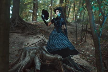 романтика: Девушка в готическом платье стоит среди коряги в лесу. В руках держит веер.