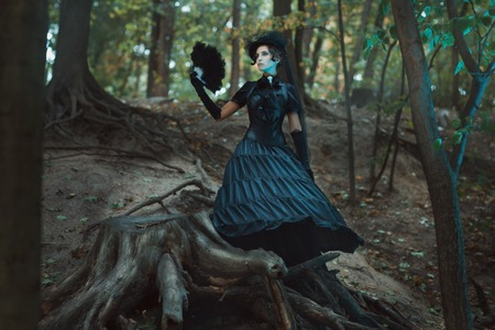 romance: 숲에 차질 사이 고딕 드레스 서 여자. 손에 팬을 보유하고있다.