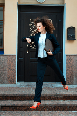 Girl in a suit running hurry. It looks like the manager arrived late. Stock Photo