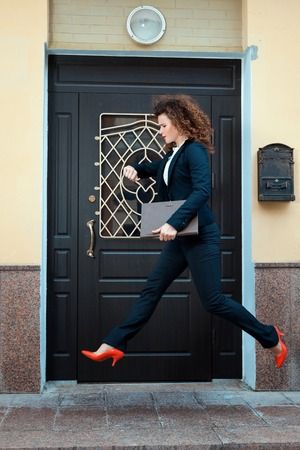 readily: Girl in a pantsuit runs in a hurry. She runs through the city streets.