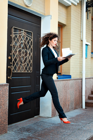 readily: Woman ran out of the office manager and in a hurry. In the hands of her documents.