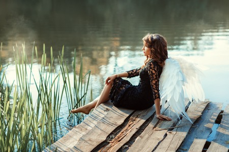 angel alone: On the pier near the river sits a girl angel. Her black dress and white wings. Stock Photo