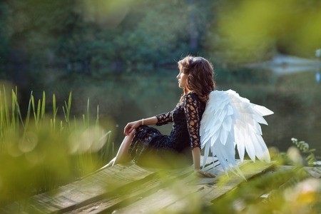 fairy woman: On the pier sits angel girl. Lake in the morning mist.