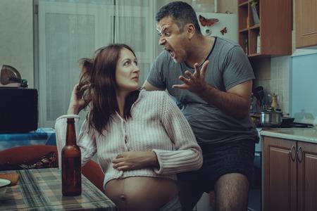 borracho: Marido borracho quiere golpear a su esposa embarazada. Él se enojó y le gritó.