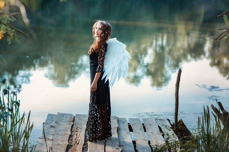 reverie: Girl with angel wings standing on the pier and smiling. This occurs in the open air on a river.