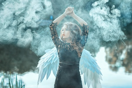 meditating woman: Girl with angel wings is shrouded in smoke. This occurs in the open air on a river.