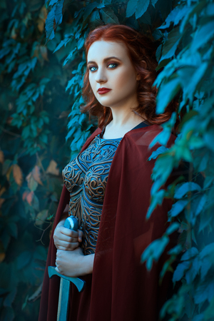 Girl with a sword standing in the bushes of grapes. The breast dressed cuirass. Stok Fotoğraf