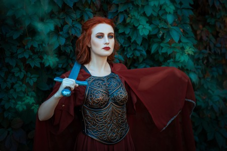 woman warrior: Red-haired girl warrior. In hands holds a sword on the chest wearing cuirass. Stock Photo