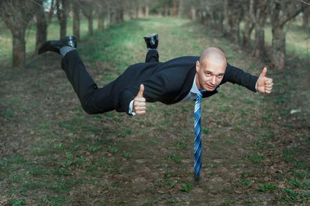 hombre cayendo: El hombre en un traje de vuelo en el parque. Sus manos mostrando signos de bien.