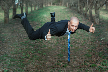 man flying: Man in a suit flying in the park. His hands showing sign of okay. Stock Photo