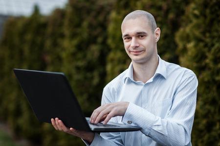 obra social: Hombre en una camisa blanca es la celebración de un ordenador portátil en su brazo. Su mano presiona el botón.