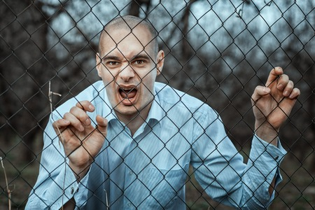 madman: Angry and fearful man grinning over the fence mesh. Hes like a madman. Stock Photo