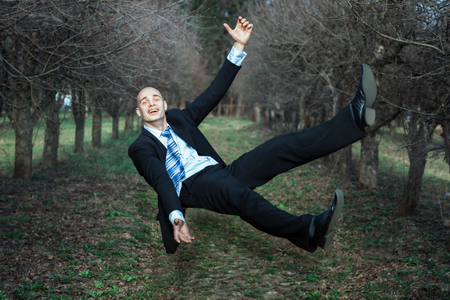 levitating: Man falls in the park. The smile on his face, he is happy.
