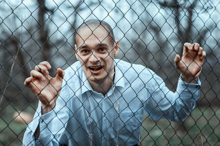 vandal: Man looks through a fence mesh. He looks like a crazy person. Stock Photo
