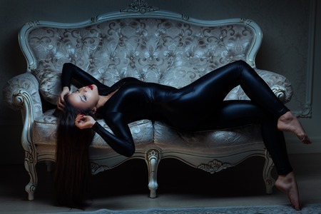 Girl in latex suit is lying on the sofa. She flirts in a dark room. Stock Photo