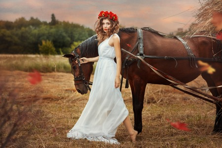 goodliness: Girl walks into the field with a horse fall. girl long white dress and red wreath on his head.