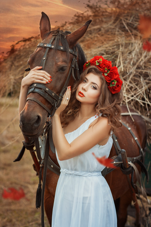Girl hugging a horses head. She is very beautiful in a white dress with a red wreath on his head.