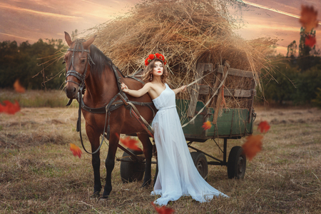 goodliness: Girl is leaning against the transport of hay. Nearby is her horse and they are in the field. Stock Photo