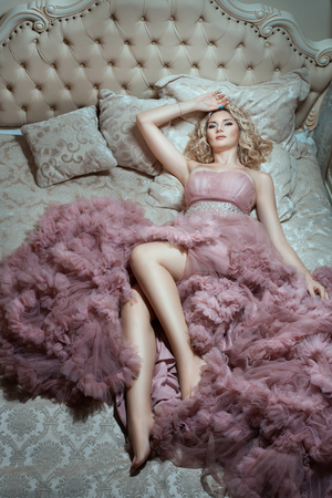 pomp: On the big bed is a  girl in a magnificent dress. Woman on top view. Stock Photo